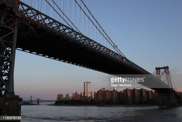 One World Trade Center is seen under the Williamsburg Bridge at sunrise on May 18 2019 in New York City