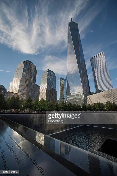 One World Trade Center stands over the National September 11 Memorial in New York US on Sunday Sept 7 2014 With building at the World Trade Center...
