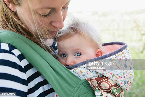 One year old baby girl in a sling on mothers front