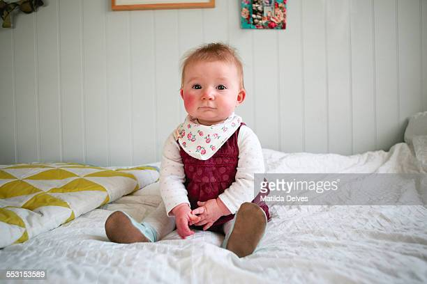 One year old baby girl, sitting on a bed