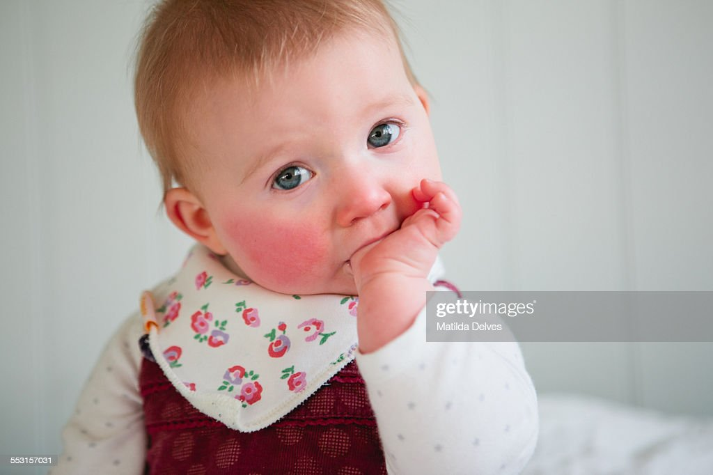 One year old baby girl sitting, sucking her thumb : Stock Photo
