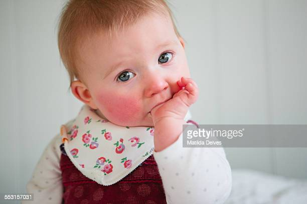 One year old baby girl sitting, sucking her thumb