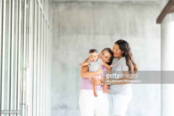 One Year Old Baby with Down Syndrome is Held by Lesbian Mom's in Concrete Structure Outdoors