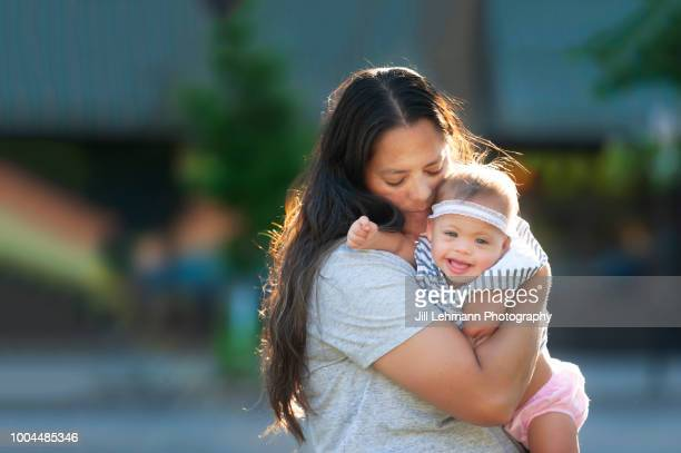 One Year Old Baby with Down Syndrome is Kissed By Mother in the Sun