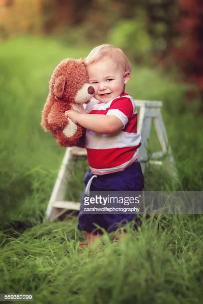 One year old boy hugging teddy bear