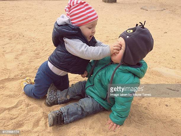one year old boys at the playground being rude - bullying escolar fotografías e imágenes de stock