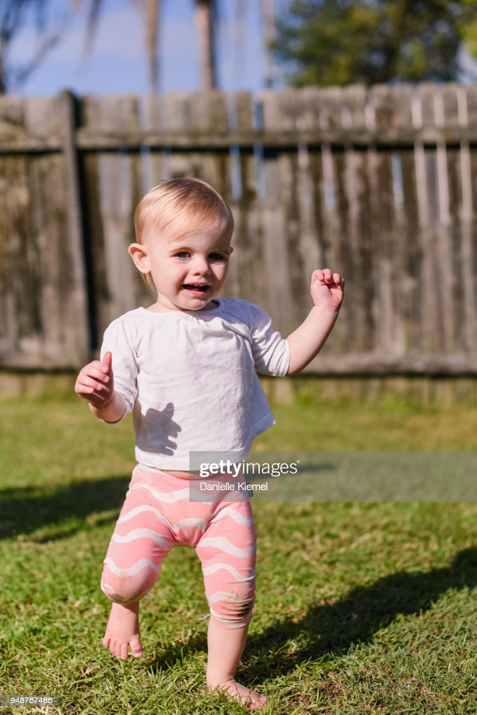 One year old child smiling and walking on grass : Stock Photo