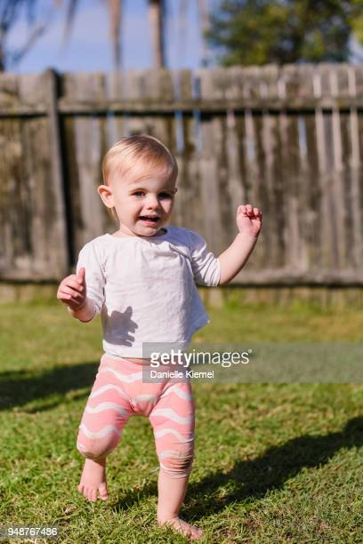 One year old child smiling and walking on grass
