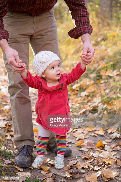 A one year old girl learns to walk with the help of her father in Kalispell, Montana.