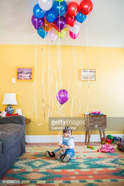 one year old girl sitting on rug with helium balloons above her