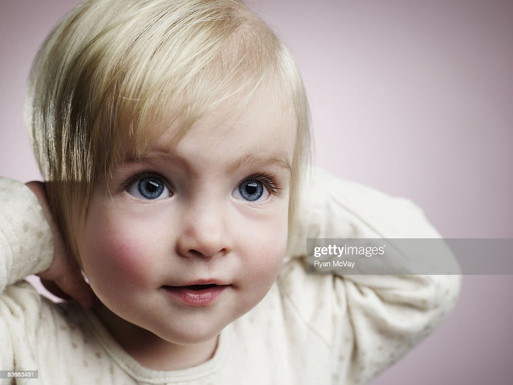 One year old girl smiling with hands over ears. : Stock Photo