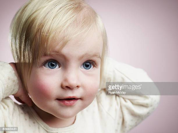 One year old girl smiling with hands over ears.