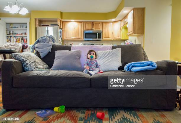 one year old sitting in middle of large sofa watching tv