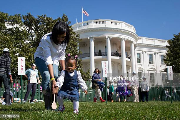 One yearold Ava Johnson plays a game during the annual White House Easter Egg Roll on the South Lawn of the White House March 28 2016 in Washington...