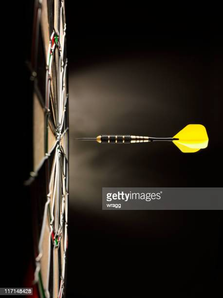 one yellow dart on target - darts stock pictures, royalty-free photos & images