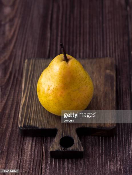 One yellow pear lying on a wooden surface