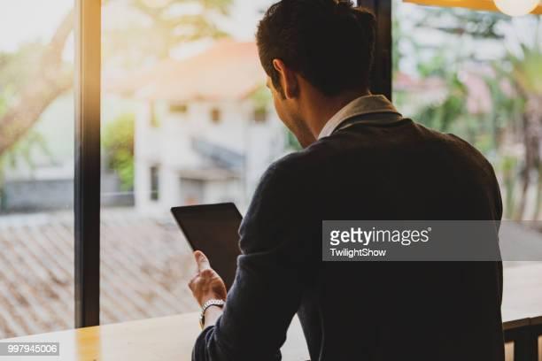 Ein junger erwachsener Mann saß mit seinem Tablet in office