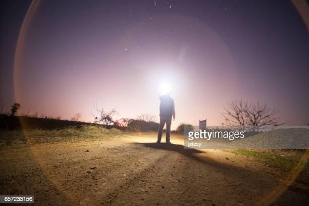 eine junge Erwachsene steht unter Himmel in der Nacht