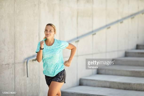 屋外で走っている一人の若いアルゼンチン人女性。 - ランニングショートパンツ ストックフォトと画像
