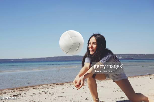 eine junge schöne frau ist volleyball am strand spielen. - strandvolleyball spielerin stock-fotos und bilder