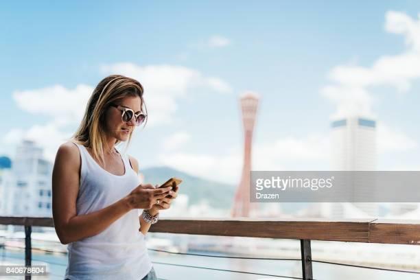 スマート フォンを使用してチェックインする一人の若い美しい女性 - 神戸市 ストックフォトと画像