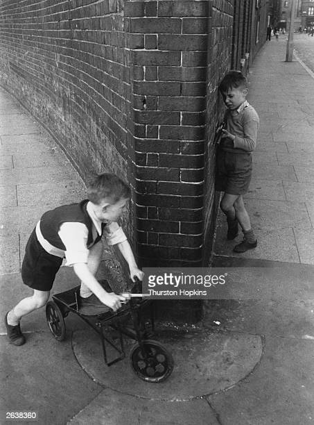 One young boy ambushing another around a street corner each holding his toy gun at the ready Original Publication Picture Post 7230 Children Of The...
