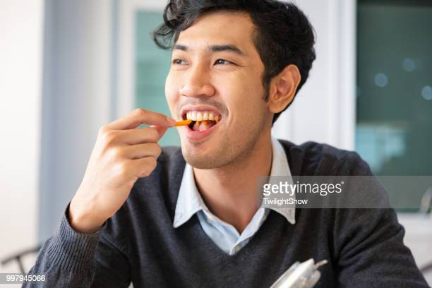 One young college students adult male taking a break sat eating snack with happiness