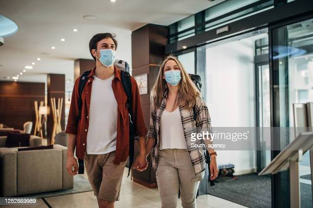 one young couple with protective face masks entering the hotel lobby - guest stock pictures, royalty-free photos & images