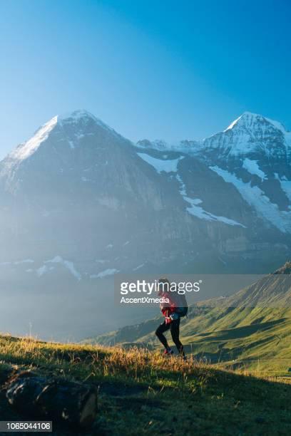 een jonge vrouwelijke wandelaar bergop loopt - hiking stockfoto's en -beelden