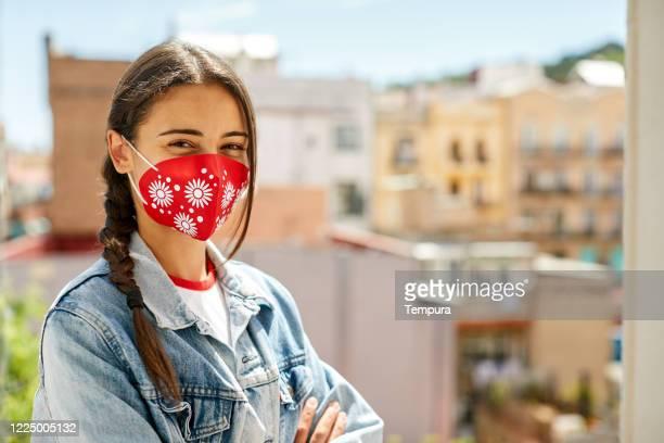 una joven mujer mirando a la cámara y usando una máscara facial - tejido partes del cuerpo fotografías e imágenes de stock