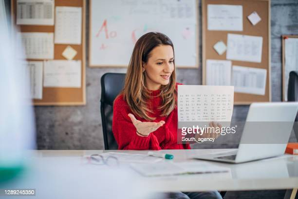 one young female professor holding online class during coronavirus pandemic - epidemic stock pictures, royalty-free photos & images