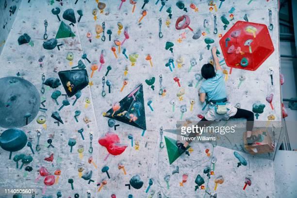 one young girl climbing a wall at a rock climbing gym - クライミングウォール ストックフォトと画像