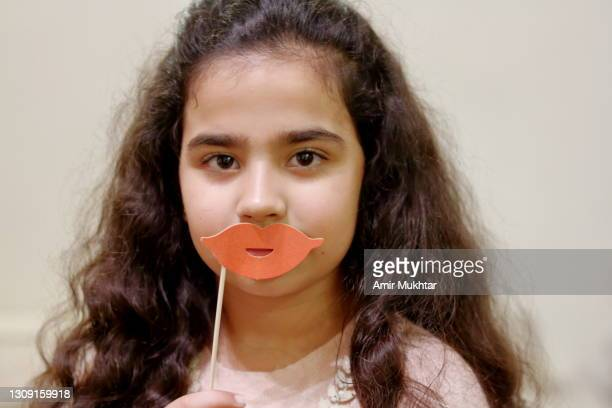 one young girl holding a pink lips prop against her lips and looking at camera. - pakistan stock pictures, royalty-free photos & images