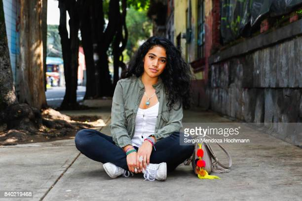 one young hispanic woman sitting crossed-legged on a sidewalk in mexico city - cross legged stock pictures, royalty-free photos & images