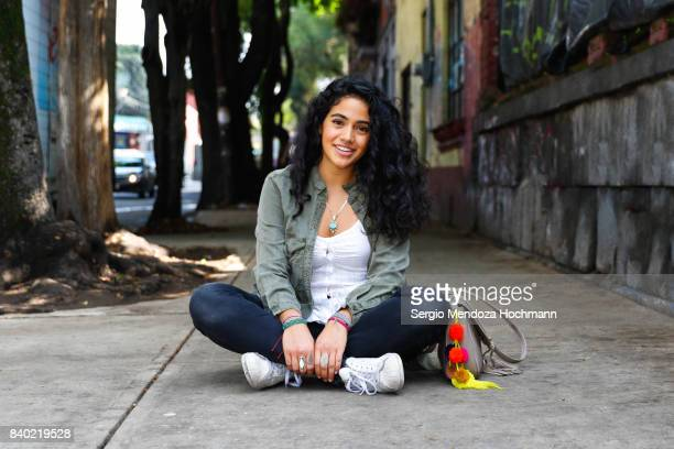one young hispanic woman sitting crossed-legged on a sidewalk in mexico city - 18 19 years stock pictures, royalty-free photos & images