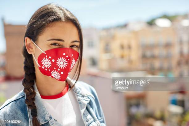 one young italian woman wearing a protective mask and smiling - reusable stock pictures, royalty-free photos & images