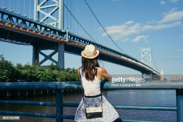one young lady under bridge enjoying river view - under skirt stock photos and pictures