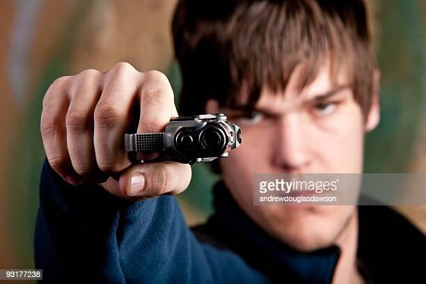 One young man aiming handgun at camera