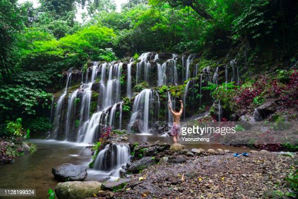 one young man explore the banyu wana amertha waterfall - behind waterfall stock pictures, royalty-free photos & images