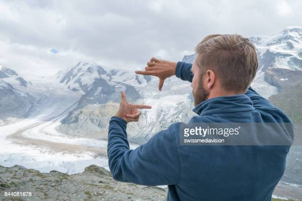 one young man framing glacier with hands, switzerland - the way forward stock photos and pictures