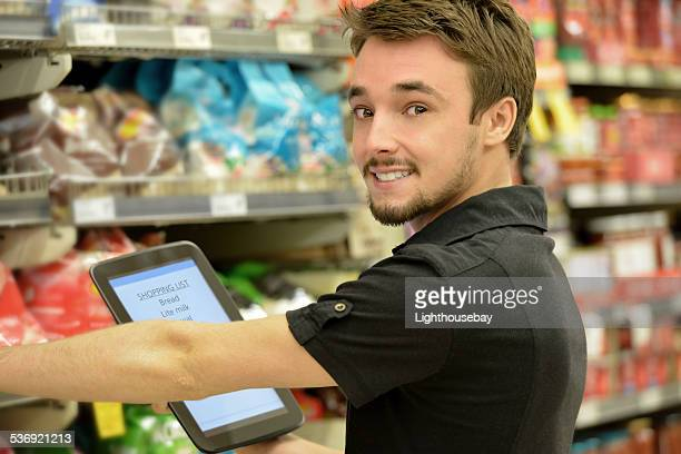 One young man shopping in supermarket using a computer tablet