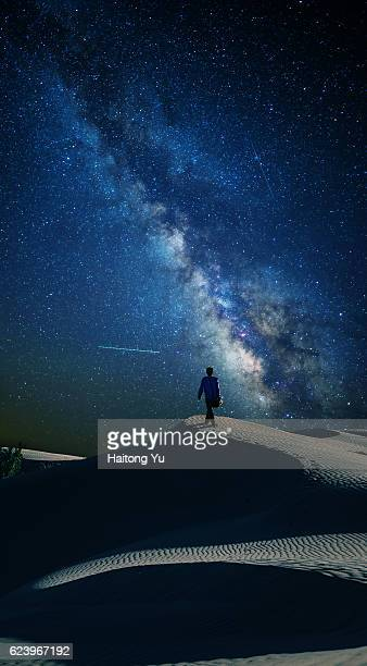 One young man trekking in desert with splendid milky way as background. Composite image.