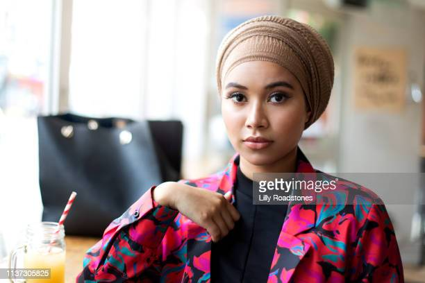 one young muslim woman sitting in cafe looking at camera - zurückhaltende kleidung stock-fotos und bilder