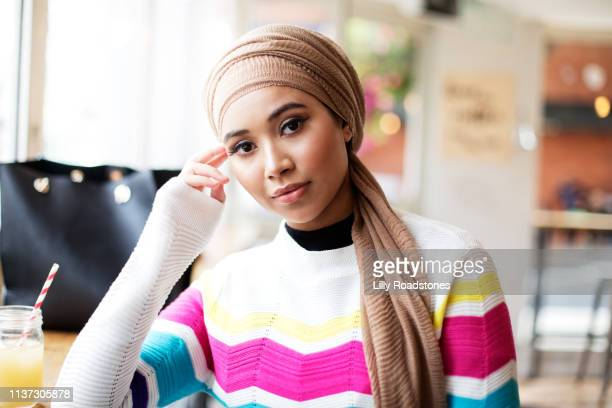 one young muslim woman sitting in cafe looking at camera - looking at camera stock pictures, royalty-free photos & images
