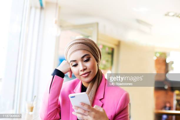 one young muslim woman using mobile phone in cafe - young women stock pictures, royalty-free photos & images