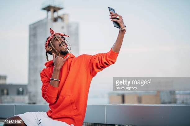 one young rapper sitting on a railing in the city and making selfie with smart phone - rapper stock pictures, royalty-free photos & images