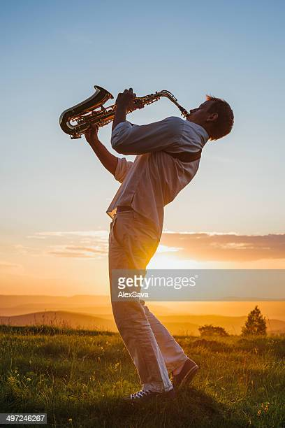 one young Saxophonist playing outdoor at sunset