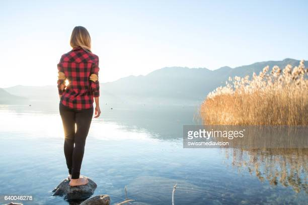 One young woman by the lake contemplating nature