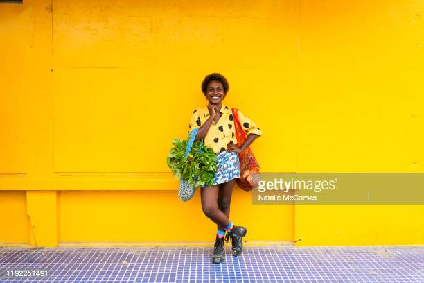 one young woman carrying grocery bags in front of yellow wall - showus stock pictures, royalty-free photos & images