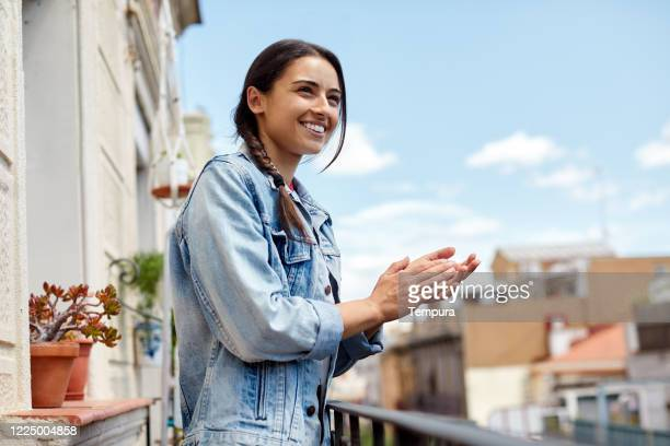 one young woman clapping and thanking the health workers from a balcony. - chanting stock pictures, royalty-free photos & images